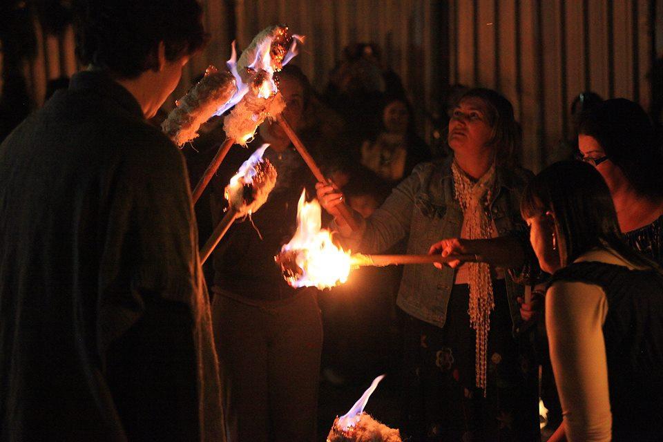 Pais e educadoras acendendo o fogo que simboliza o conhecimento